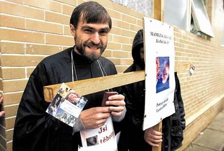 S improvizovaným křížem, knihou žalmů a plakátky proti interrupcím stává kněz Libor Halík před fakultní porodnicí na Obilním trhu v Brně.