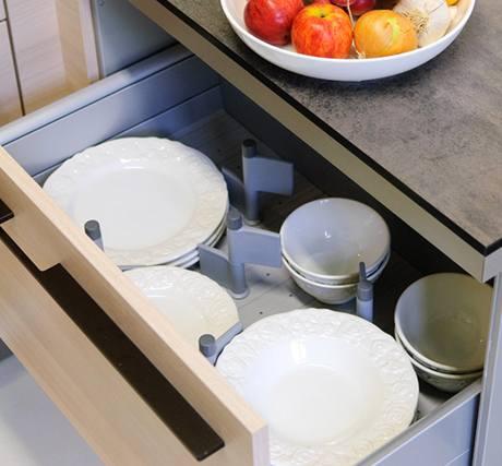 """V dosahu myčky i sporáku jsou talíře. Pracovní """"skleněné"""" deska z tvrzeného laminátu vypadá velmi efektně"""