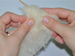 Nejprve si na špejli natvarujte kousek bílého ovčího rouna jako základ tělíčka.