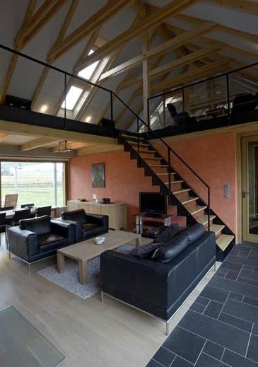 Výtvarný výraz interiéru vytvářejí stropní trámy, otevřený krov i černá konstrukce schodiště a zábradlí