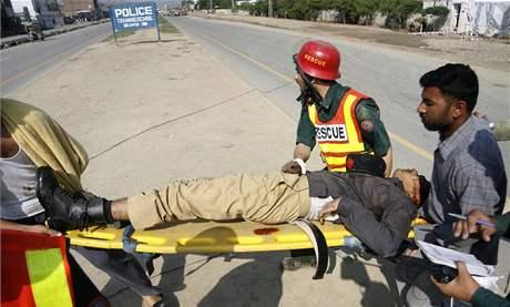 Záchranáři přenášejí zraněného policistu poté, co neznámí ozbrojenci napadli policejní výcvikové centrum v Láhaur. (30. března 2009)