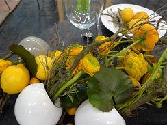 Zelenožlutooranžovou kombinaci projasňují bílé vázy ve tvaru koule, pryskyřníky a minigerbery ladí s citrony a malými pomerančíky kumkvaty. Větvičky s nádechem nazlátlého mechu vše barevně dokreslují,  voňavé tóny dodávají bylinky, především rozmarýna.