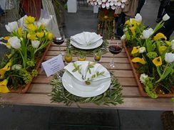 Slunné Středomoří je nekonečně inspirující. Větvičky starobylých oliv symbolizují prostírání, motiv se opakuje i na ubrousku. Květinová výzdoba lemuje kraje stolu. Bílé, zelené a žluté to ladí i s červeným vínem.