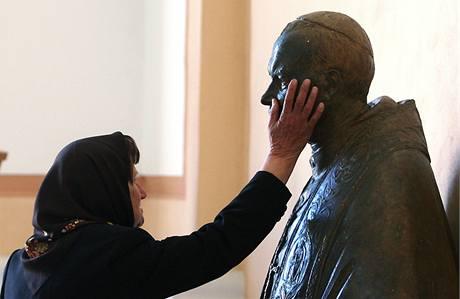 Jedna z věřících se modlí k soše papeže Jana Pavla II. v severoalbánském městečku Shkoder.