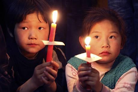 Děti se svícemi v rukou poslouchají velikonoční mši v čínském městě Tianjin.