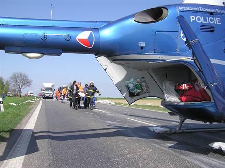 Záchranáři odnáší zraněného řidiče mercedeseu, jehož vůz zasáhla role papíru, která se uvolnila z kamionu u Bratonic na Mladoboleslavsku (14. dubna 2009)