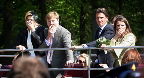 Nizozemský korunní princ Willem-Alexander a jeho manželka princezna Máxima (vlevo) zděšeně sledují, jak řidič osobního vozu projíždí davem při slavnostním průvodu. (30. dubna 2009)