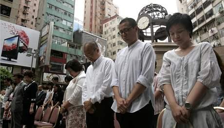 Čína si dnes připomíná ničivé zemětřesení v provincii S'-čchuan. Na snímku lidé v Hongkongu uctívají oběti minutou ticha.(12. května)