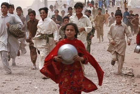 Děti si v pákistánských uprchlických táborech běží pro příděl humanitární pomoci