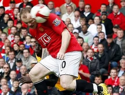Manchester United - Arsenal: Domácí útočník Wayne Rooney (v červeném) předskočil Bacaryho Songu