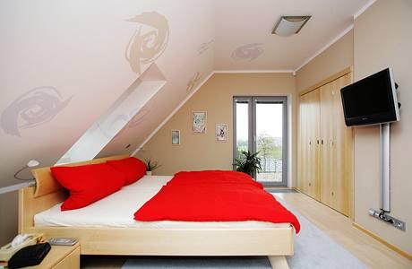 Ložnice rodičů v jemné barevnosti a s individuálně pojatou dekorací na zkosených stěnách