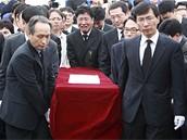 Lidé vynášejí ostatky bývalého prezidenta z nemocnice.