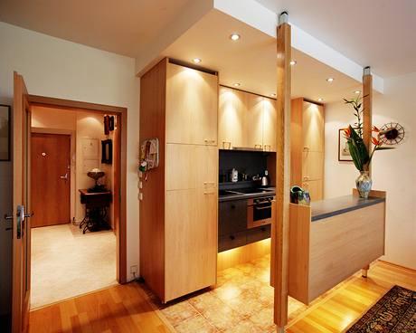 Podsvícením skříněk i použitým materiálem na čelních plochách kuchyně vhodně navazuje na obytný prostor