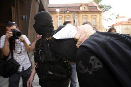 Policisté přivádějí neonacistu k výslechu.