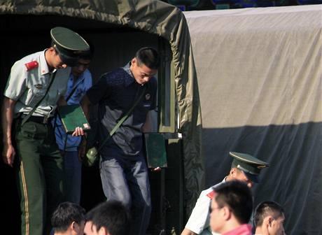 Polovojenské jednotky vystupují z nákladních aut u bran Zakázaného města poblíž náměstí Tchien-an-men. (4. června 2009)