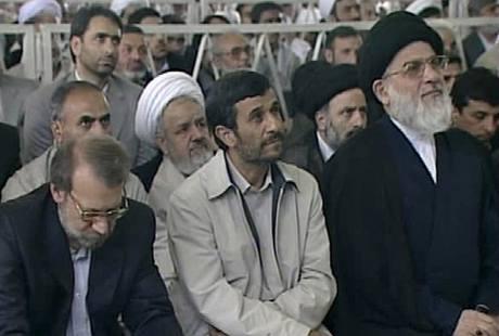 Íránský prezident Mahmúd Ahmadínežád naslouchá projevu nejvyššího duchovního Chameneího (19. června 2009)