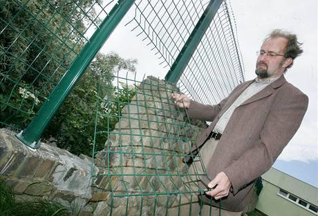 Severočeský mluvčí ČEZ ukazuje vystřihanou díru v plotě elektrárny Prunéřov II (10. června 2009)