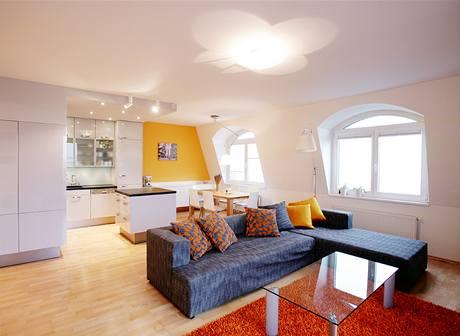 Obývací části dominuje rohová sedačka, kuchyně v šedé barvě splývá se stěnami