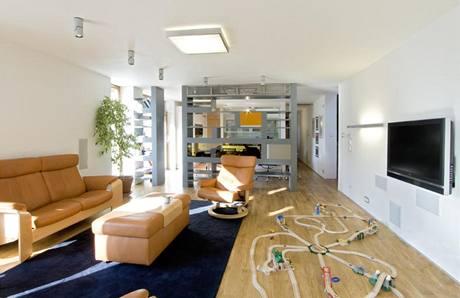 Knihovna zhotovená na míru z MDF desek rozděluje velký společný prostor na jídelní část a sezení