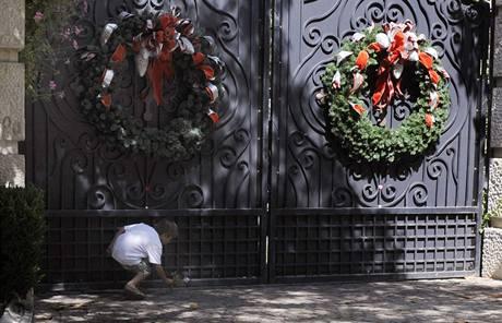 Sedmiletý Ryan Mossell pokládá květinu před branou Jacksonovy rezidence (25. června 2009)