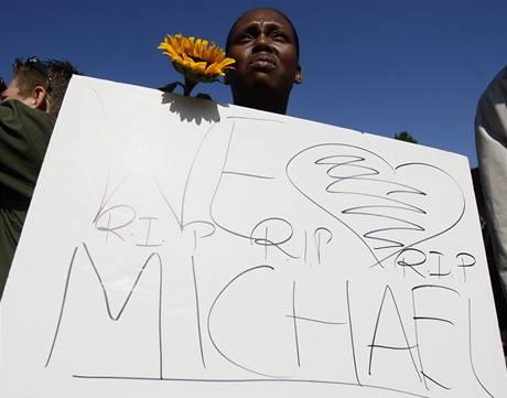 Milujeme Tě. Odpočívej v pokoji, Michaeli, hlásí cedule Jacksonova fanouška (25. června 2009)