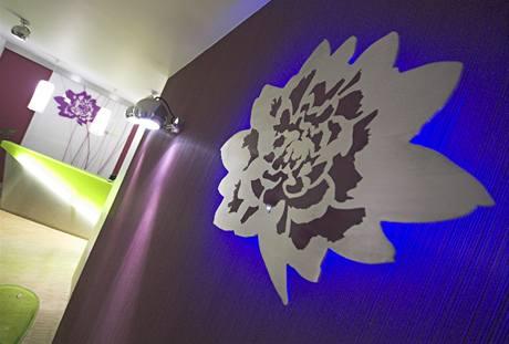 Stěna je tapetovaná purpurovým reliéfním vinylem