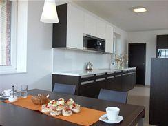 Kuchyňskou linku od sezení odděluje pultový korpus, v němž je integrováno mycí centrum