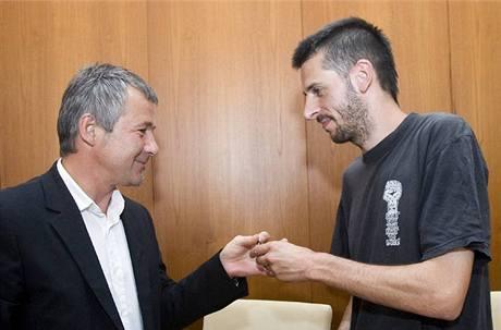 Majitel objektu Petr Svinka předává klíče mluvčímu squaterů Janu Němcovi