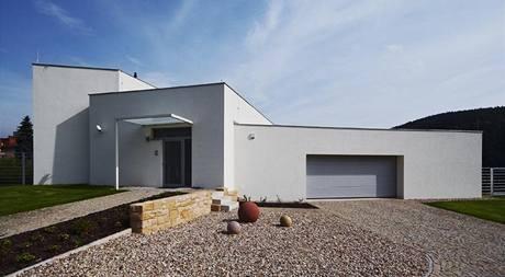 Při pohledu z ulice je zřetelná kompozice odstupňování výšek od garáže s nejnižším stropem přes střední obytnou část až po dvoupodlažní křídlo