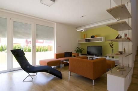 Relaxační část obývacího pokoje designéři oddělili od schodiště policemi zavěšenými na ocelových lankách