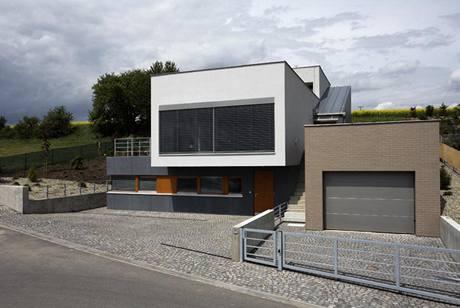 Přízemní část je obložena cembonitovými deskami, garáž cihelnými pásky, obytná část vystupuje bíle omítnutou hmotou