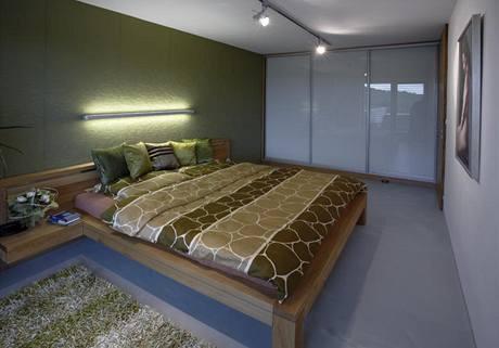 Čelní stěnu zdobí tapeta s plastickým vzorem, dubová postel byla vyrobena na zakázku