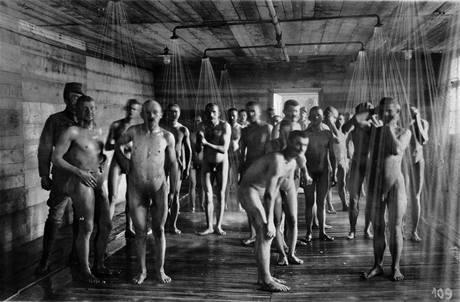 Italští zajatci, kteří byli předtím odvšiveni, se sprchují pod dohledem rakousko-uherské stráže.