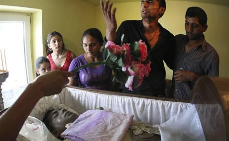 Příbuzní romského mladíka Iona Micleska truchlí nad rakví s ostatky vystavenou v jeho rodném domě.. (8. 8. 2009)