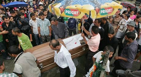 Pohřeb rumunského Roma Iona Micleska. Mladíkovo tělo rodina naložila na korbu nákladního vozu, který zdobily květiny, větve jehličnanů a věnce. (9. 8. 2009)