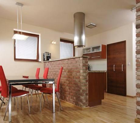 Kuchyňská linka s příjemnou třešňovou dýhou se ukrývá za barovou zídkou