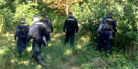 Policisté prohledávají okolí místa vraždy v Kunraticích. (17. srpna 2009)