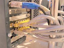 Deset monitorů připojených LAN kabely do switche v hlavním (a jediném) počítači