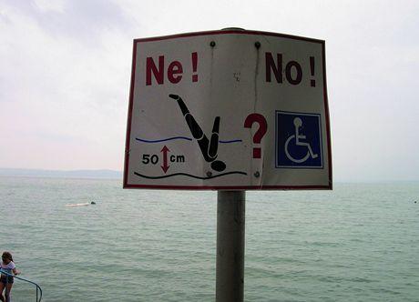 Maďarsko, Balaton. Malá hloubka - na jižním pobřeží (toto je konkrétně u Siofoku) opravdu nenáí možné skákat do vody šipky. Cedule hovoří výstižně, a nemusíme ani umět maďarsky.