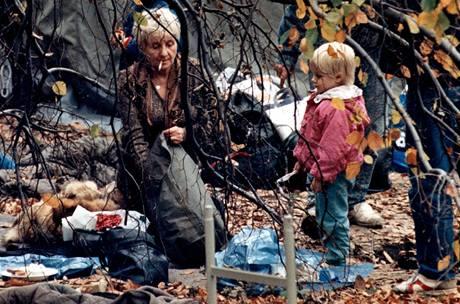 Vůle a zima. Starší paní, uprchlice z NDR, na zahradě ambasády SRN, se svěřeným dítětem pečuje o svoje zavazadlo po noci strávené na kavalci v popředí snímku - při teplotě 8 stupňů Celsia; Praha 4. listopadu 1989.