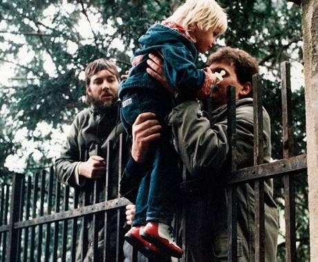 Neboj se, bude to dobré. Uprchlíci pobývající již na zahradě ambasády SRN přebírají dítě, jehož matka je ještě mimo území velvyslanectví, Praha 3. října 1989.
