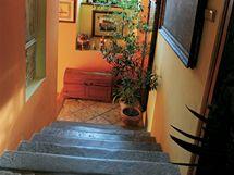 Kamenné schodiště s obrazy nepůsobí díky výmalbě chladně