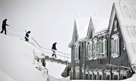 Vymrzlí turisté se jdou ohřát do restaurace na vrcholu švýcarské hory Saentis. (14. října 2009)