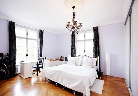 Ložnice i díky dvě oknům, vysokým stropům a bílé barvě působí hodně vzdušným dojmem