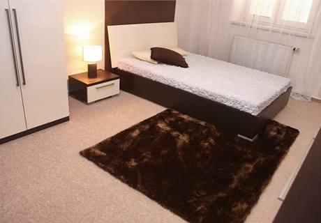 Světlý celoplošný koberec vedle postele doplňuje tmavě hnědý kusový, který je sladěn s rámem postele ze dřeva wengé