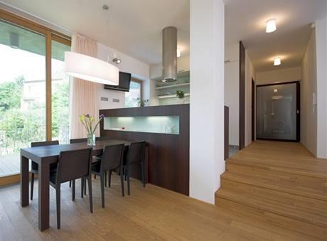 Poloha kuchyně ve zvýšené úrovni interiéru dovoluje skrýt pracovní plochy pohledu stolujících
