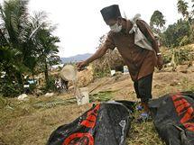 Pohřeb obětí po ničivém zemětřesení na Sumatře. Příbuzní tradičně symbolicky polévají těla mrtvých vodou, aby je během pohřbívání očistili. (8. října 2009)