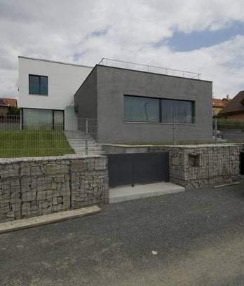 Stavba je oddělena od ulice gabionovou zídkou, vstupní branka ladí s architekturou stavby