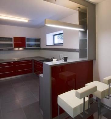 V kuchyni promlouvají moderní materiály a technologie – šedé lakované MDF desky v provedení s vysokým leskem, pracovní deska z Corianu, skleněné obložení pracovní plochy