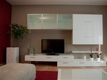 Původní pokojovou stěnu nahradil bílý nábytek, který tvoří kontrast k béžovým a vínovým stěnám